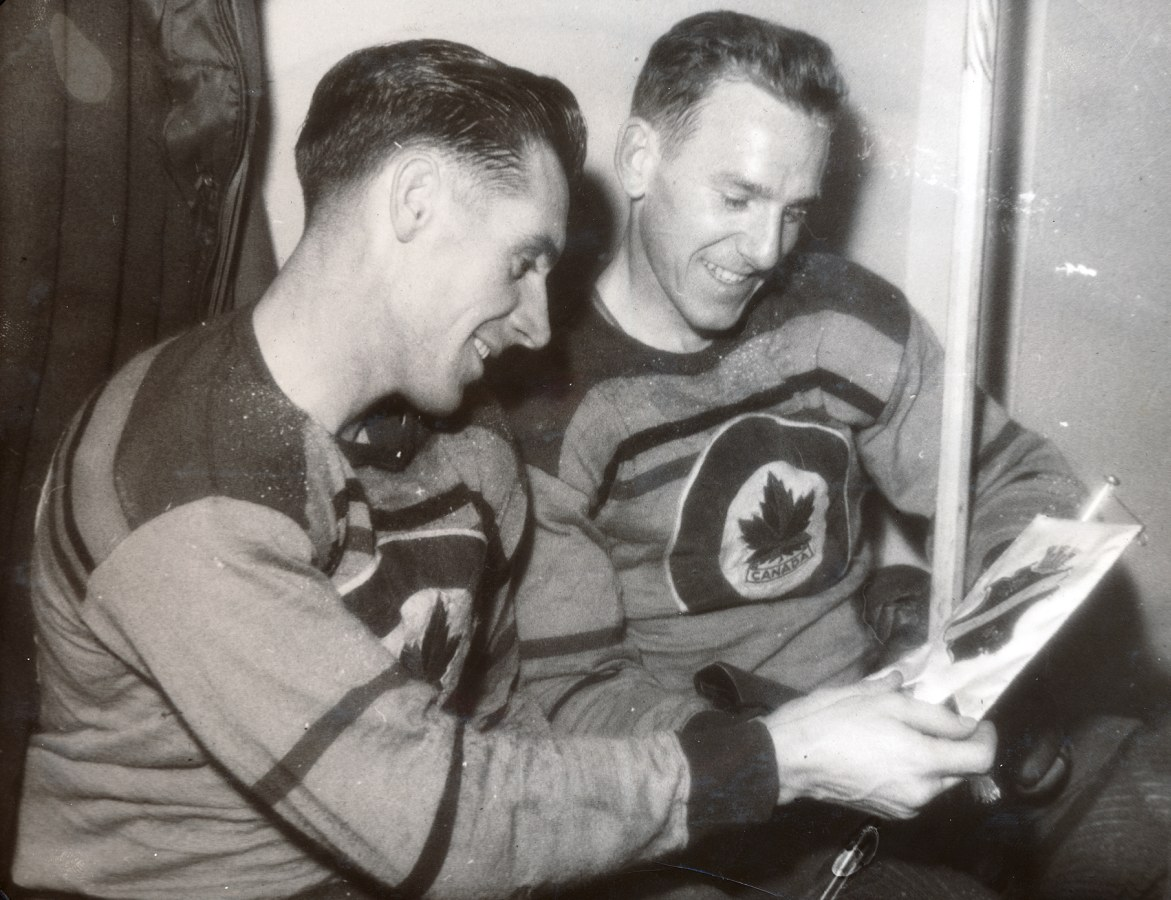 Photo: RCAF Flyers Schroeter and Renaud Look at a Momento Gift from the Swedish Hockey Club