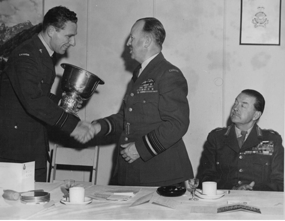 Photo: RCAF Flyer Team Manager S/L Sandy Watson presents the World Amateur Hockey Cup to Air Marshall Wilf Curtis, chief of air staff.