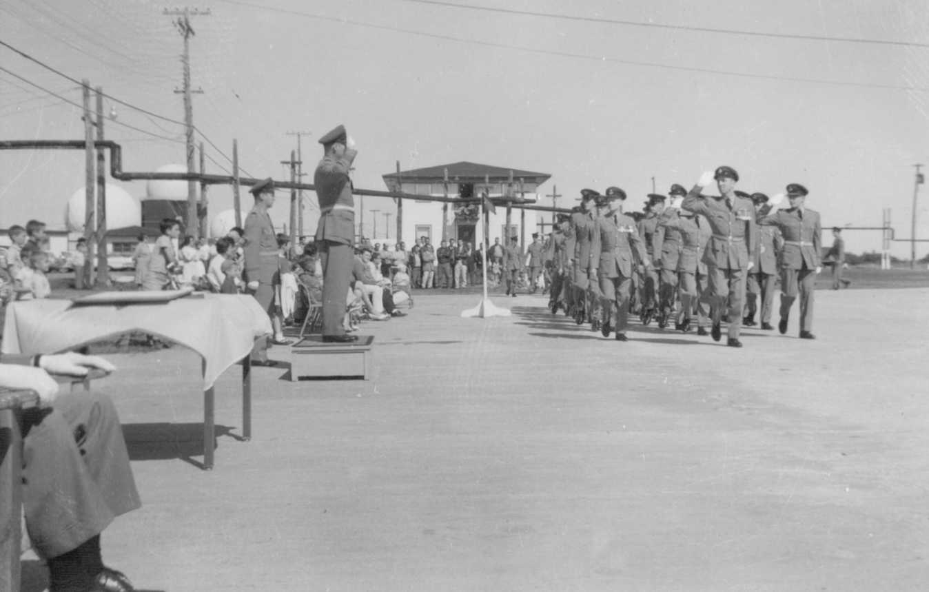 Photo: W/C Hubert Brooks takes salute as Station Airman led by S/L Ralph MacWilliam March Past
