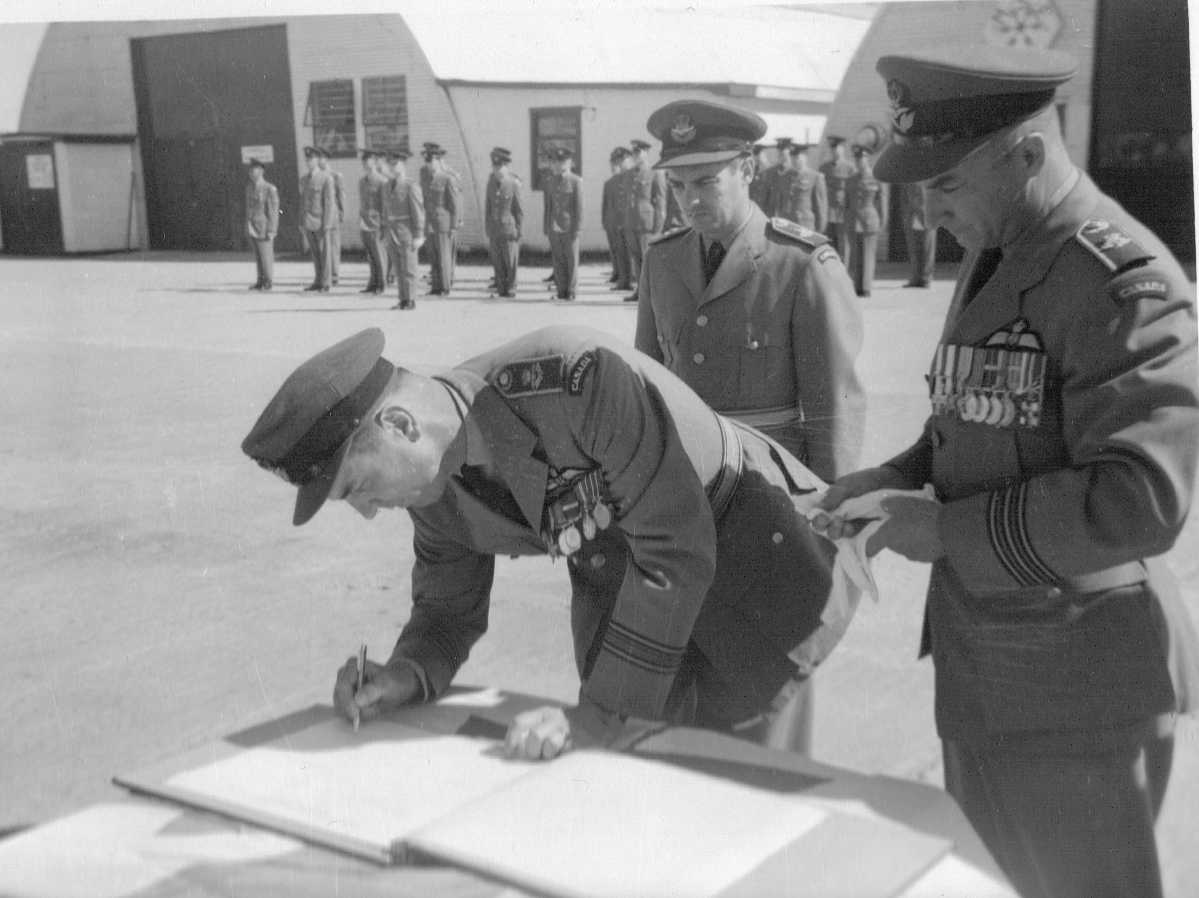 Photo: S/L R. McWilliam signs transfer of command documet for RCAF moisie while W/C H. Brooks looks on